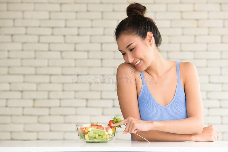 Asiatisk kvinna i glade ställingar med salladbunken på sidan arkivfoton
