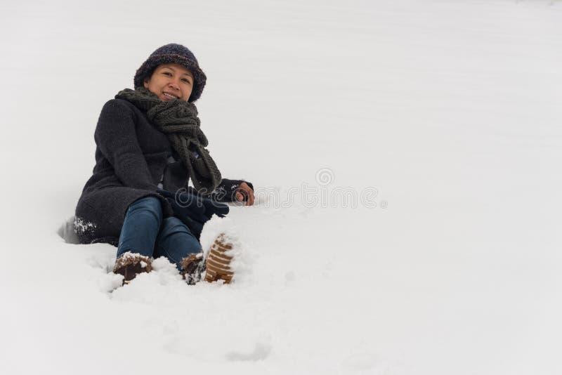 Asiatisk kvinna i hatt som lägger i snö arkivfoto