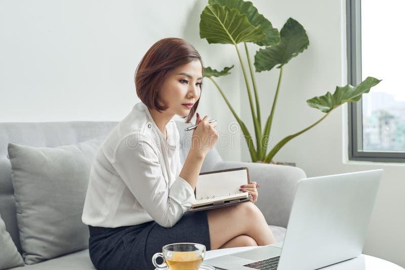Asiatisk kvinna i kaf? genom att anv?nda b?rbara datorn och att notera n?gra data p? notepaden royaltyfria bilder