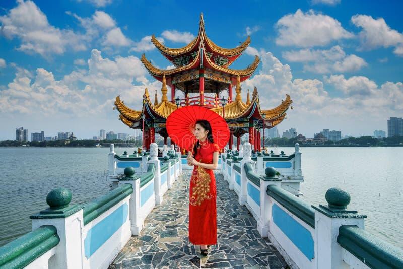 Asiatisk kvinna i kinesisk klänning som traditionellt går på Kaohsiungs berömda turistattraktioner i Taiwan royaltyfria foton