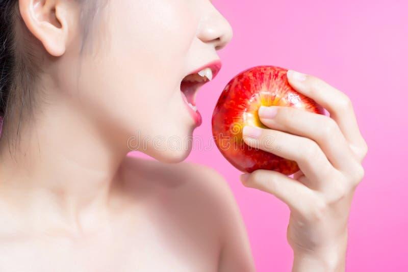 Asiatisk kvinna med äpplebegrepp Henne som ler och rymmer äpplet Skönhetframsida och naturlig makeup lätt för dig färgar ändring  royaltyfria bilder