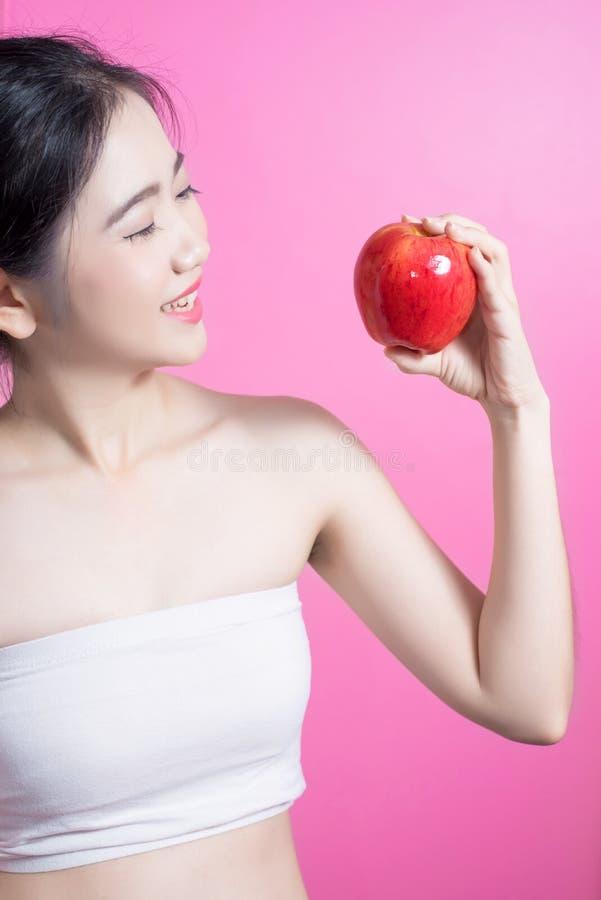 Asiatisk kvinna med äpplebegrepp Henne som ler och rymmer äpplet Skönhetframsida och naturlig makeup lätt för dig färgar ändring  arkivbilder