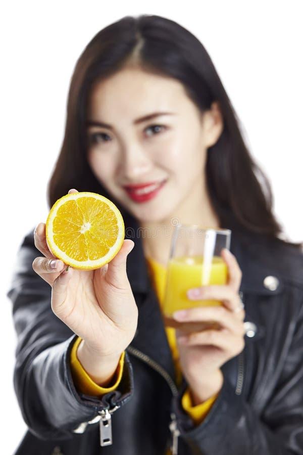 Asiatisk kvinna med apelsinen och fruktsaft royaltyfria foton