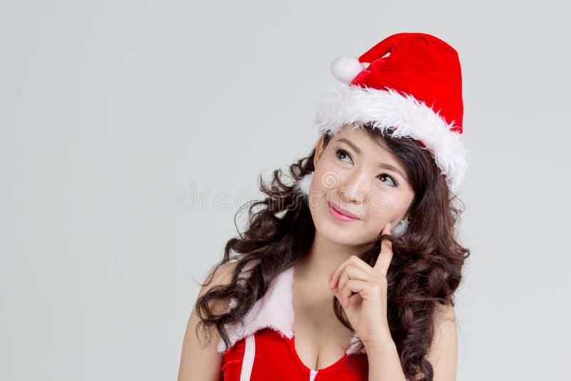 Asiatisk kvinna med att tänka för santa klänning royaltyfria foton