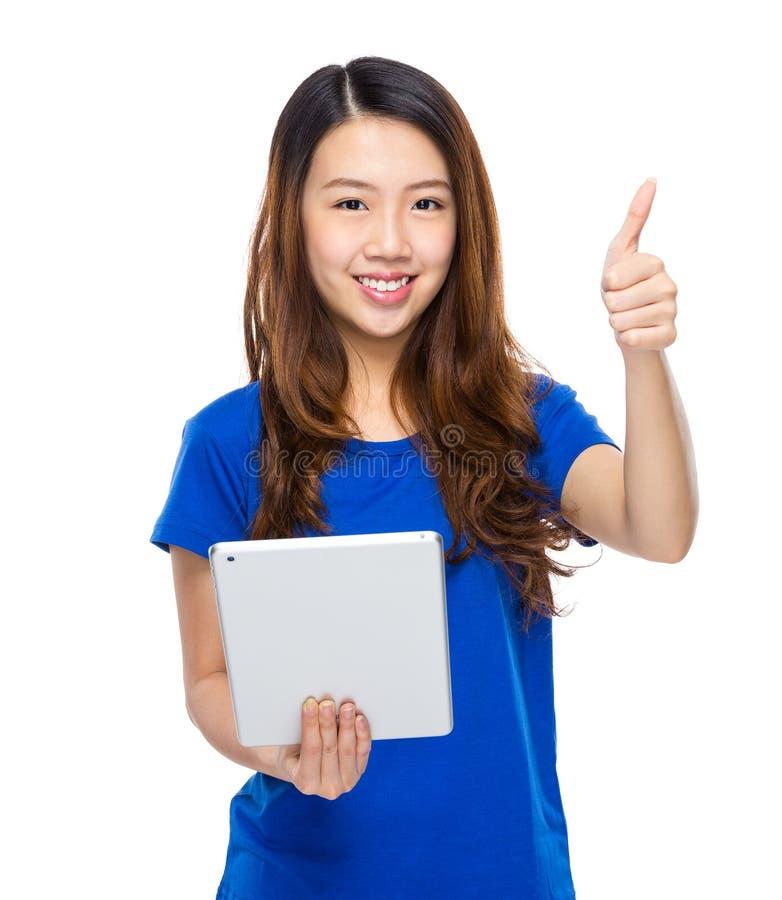 Asiatisk kvinna med den digitala minnestavlan och tummen upp arkivbild