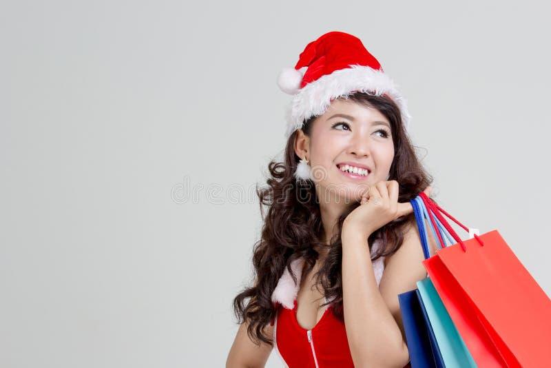Asiatisk kvinna med den santa klänningen som rymmer färgrika shoppingpåsar royaltyfri foto
