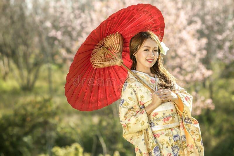 Asiatisk kvinna med den traditionella kameleonten för klänning och det röda paraplyet royaltyfri fotografi