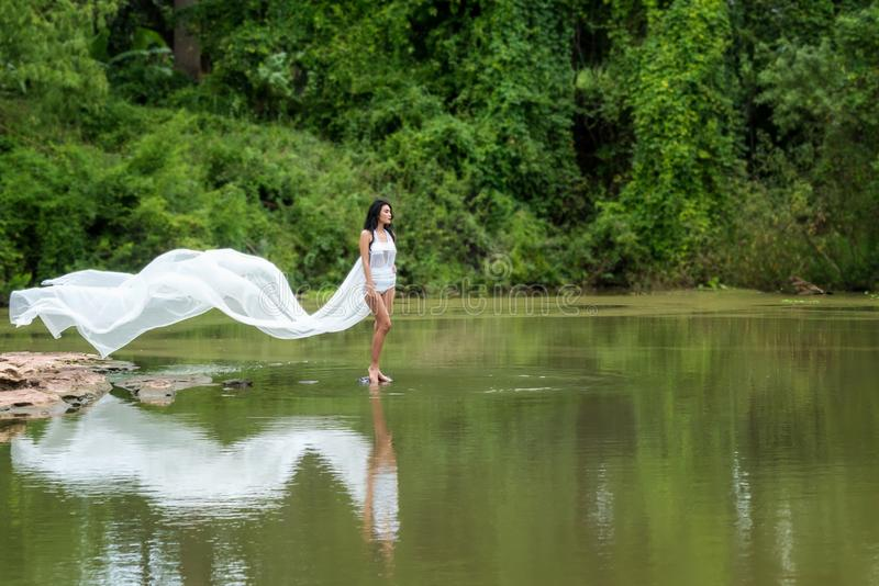 Asiatisk kvinna med den vita klänningen som kopplar av och står på den tropiska exotiska floden med fantastiskt färgvatten för tu arkivbilder