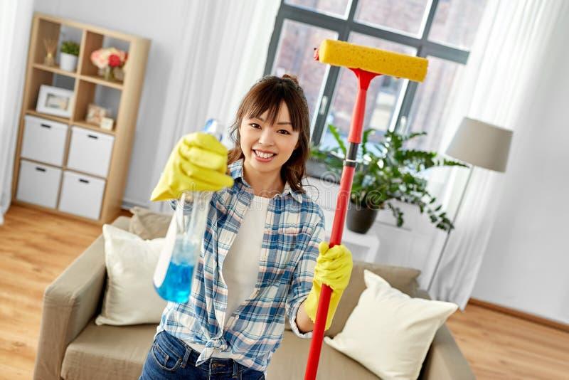 Asiatisk kvinna med fönsterrengöringsmedlet och svampgolvmopp royaltyfri fotografi