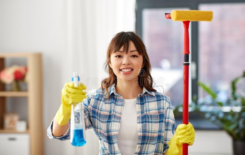 Asiatisk kvinna med fönstertvättmedel och svampgolvmopp fotografering för bildbyråer