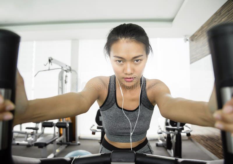 Asiatisk kvinna med hörlurar på motionscykelen arkivfoto