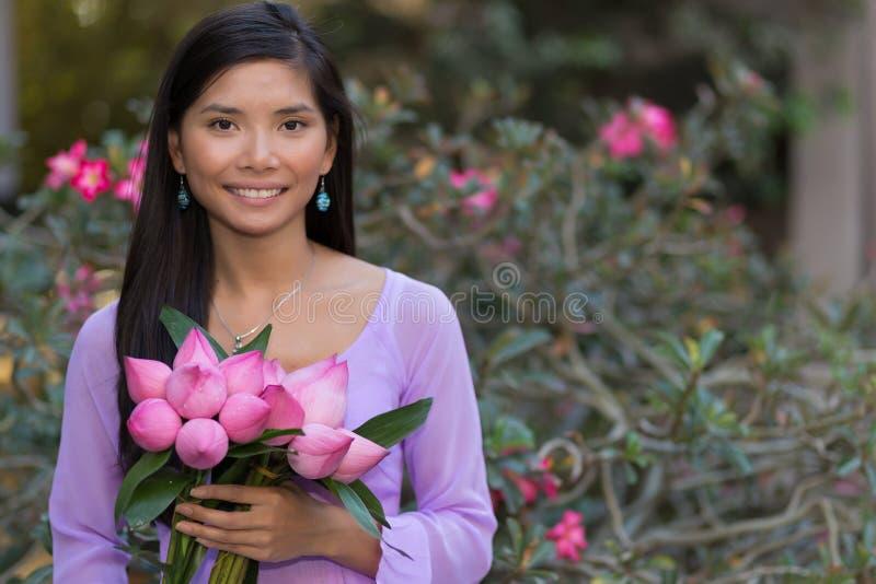 Asiatisk kvinna med lotusblommablommor arkivfoton