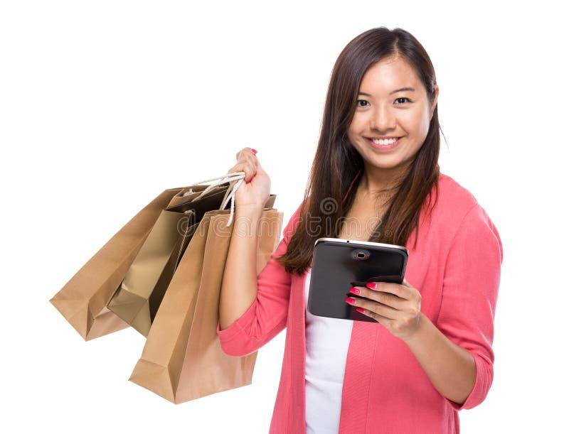 Asiatisk kvinna med minnestavlan och shoppingpåsen royaltyfria bilder