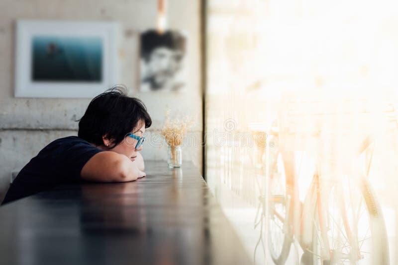 Asiatisk kvinna med monokeln som väntar i coffee shop royaltyfria bilder