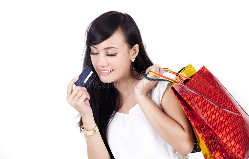 Asiatisk kvinna med shoppingpåsen och en kreditkort royaltyfri foto