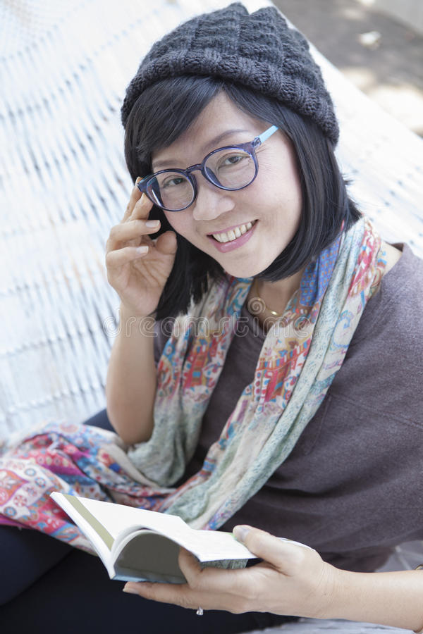 Asiatisk kvinna och fick- bok i handen som kopplar av på hem- vagga royaltyfria foton