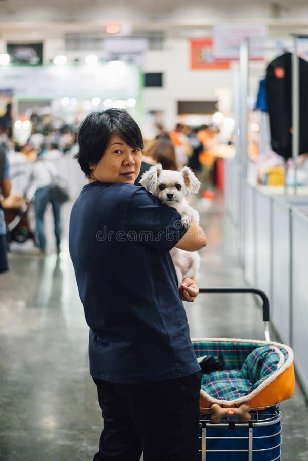 Asiatisk kvinna och hunden i utställningskorridor eller expo royaltyfri fotografi