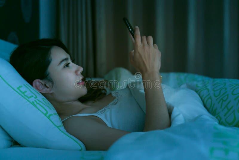 Asiatisk kvinna på säng sent på natten som smsar genom att använda mobiltelefongummihjulet royaltyfri fotografi