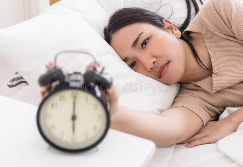 Asiatisk kvinna på säng som ut når för att stoppa ringklockan arkivbild