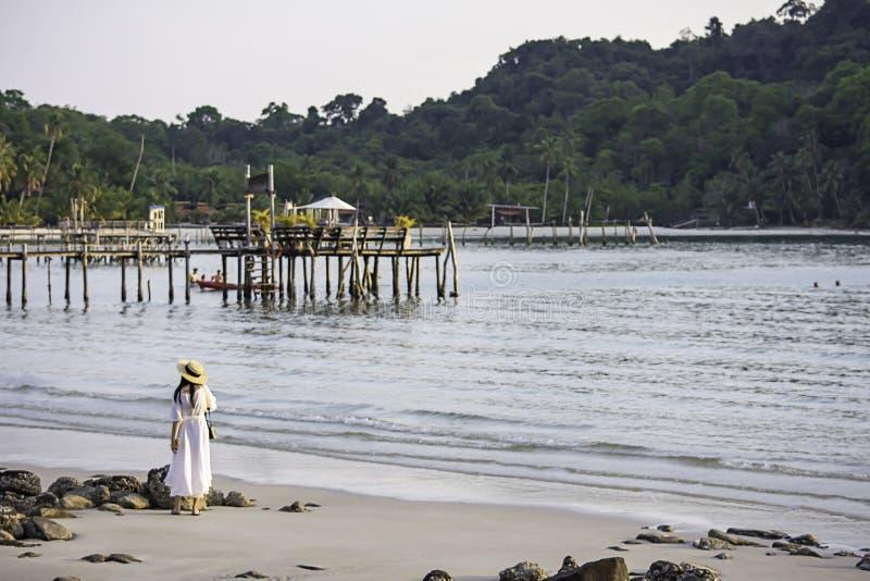 Asiatisk kvinna på stranden bakgrundshavet och en träbro på Koh Kood, Trat i Thailand arkivfoton