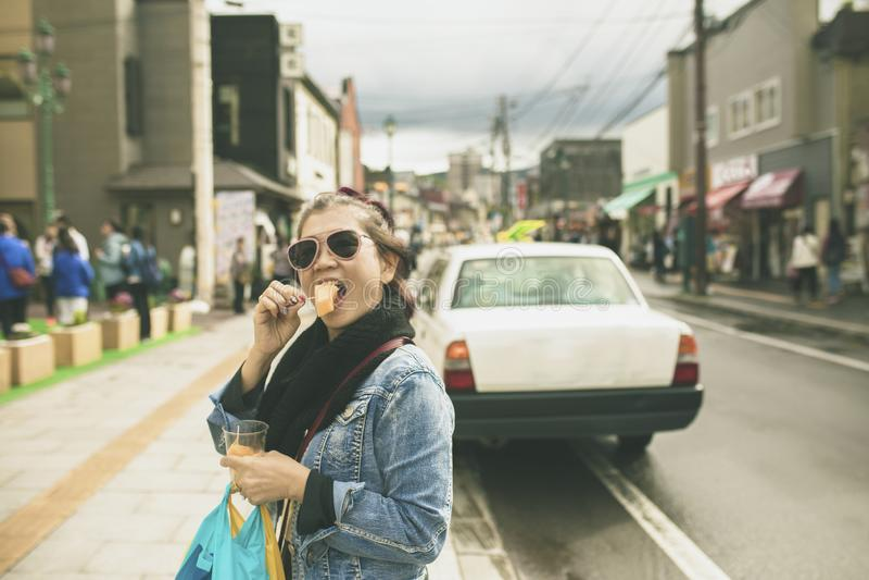 Asiatisk kvinna som äter den hokkaido melon på otaru gata en av mest po fotografering för bildbyråer