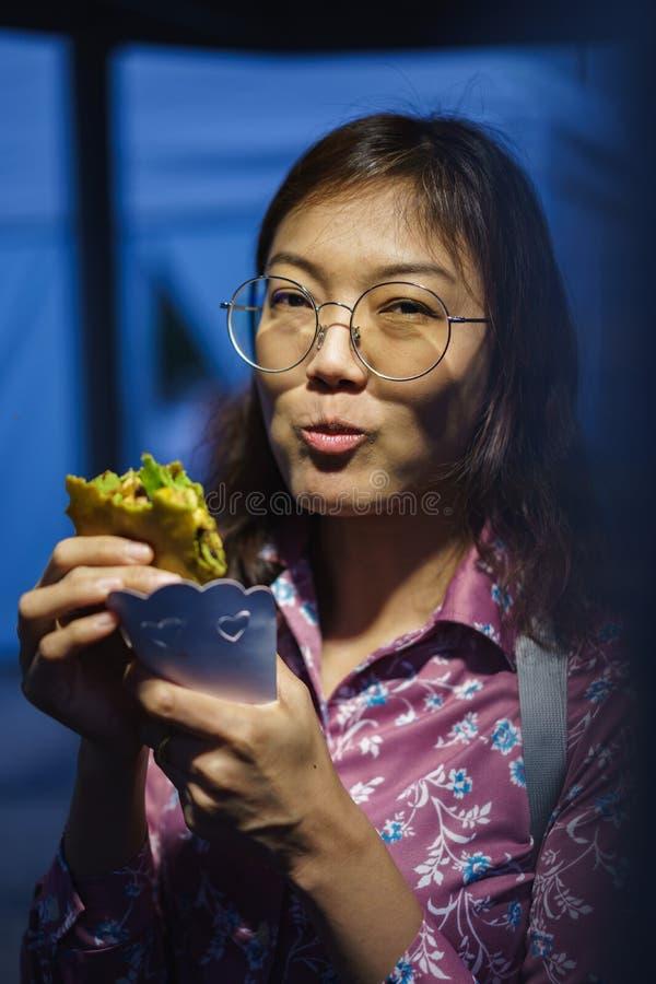 Asiatisk kvinna som äter kräpp royaltyfria foton