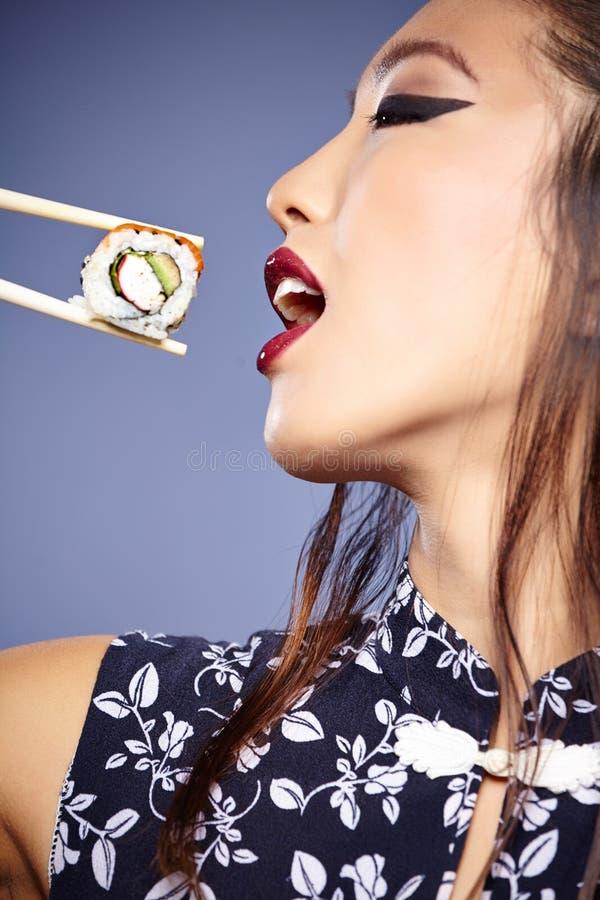 Asiatisk kvinna som äter sushi, royaltyfria bilder