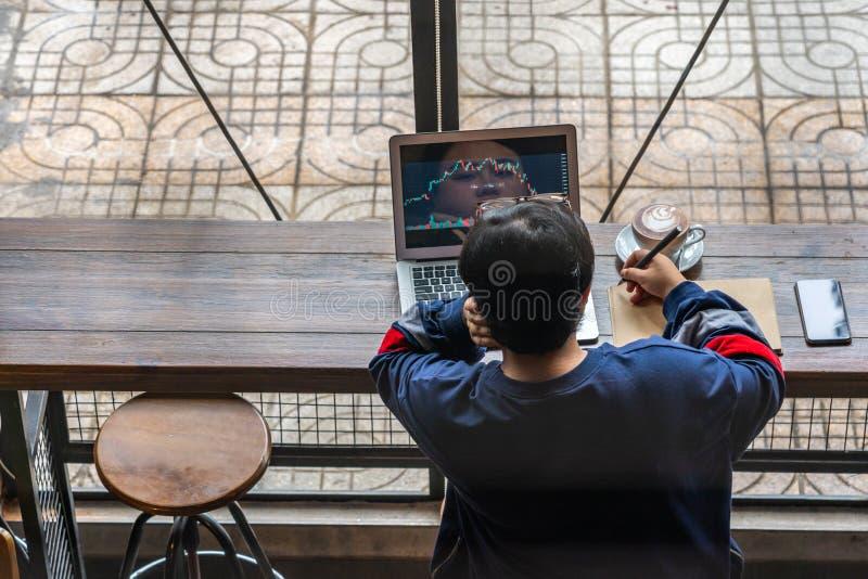 Asiatisk kvinna som analyserar den finansiella ljusstakegrafen på bärbara datorn på kafeterian royaltyfri foto
