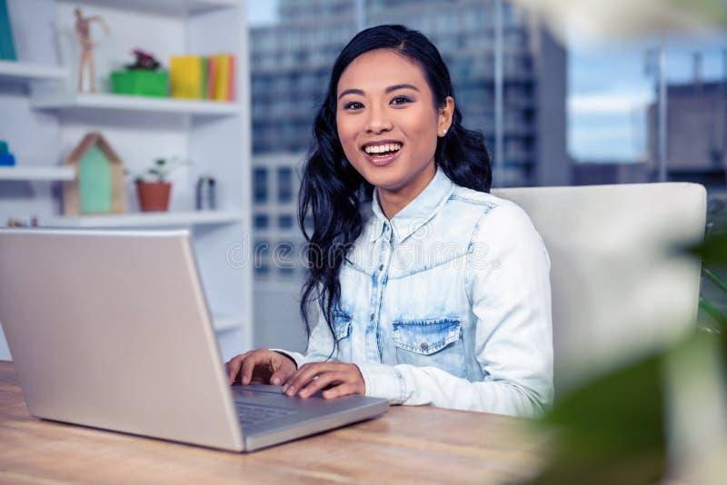 Asiatisk kvinna som använder bärbar dator fotografering för bildbyråer