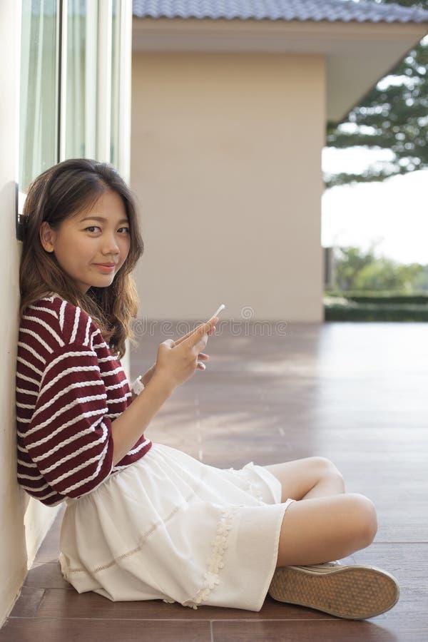 Asiatisk kvinna som använder den smarta telefonen i handen som ser med ögonkontakten arkivbild