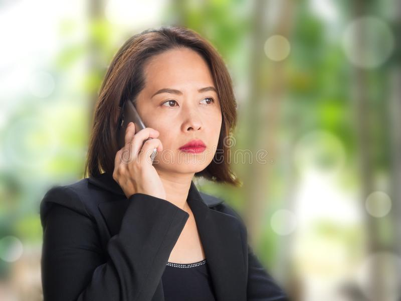 Asiatisk kvinna som använder den smarta telefonen med bakgrund för suddighetsgräsplanträdgård royaltyfri foto