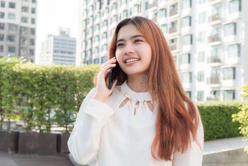 Asiatisk kvinna som använder den smarta telefonen på suddig bakgrund av residentien royaltyfria foton
