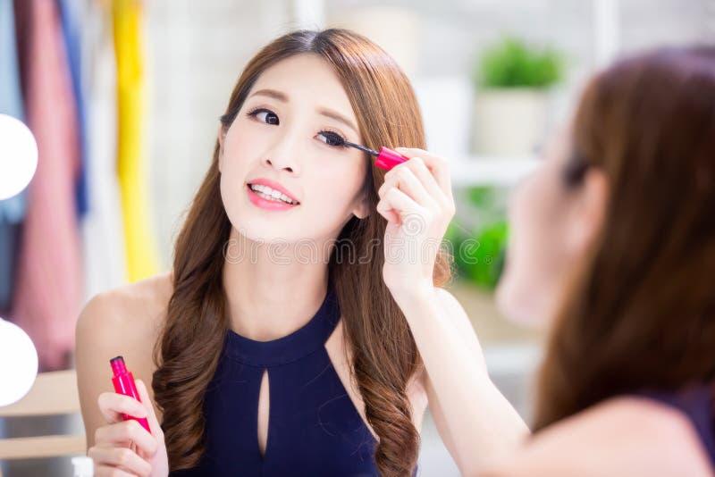Asiatisk kvinna som använder mascara royaltyfri foto