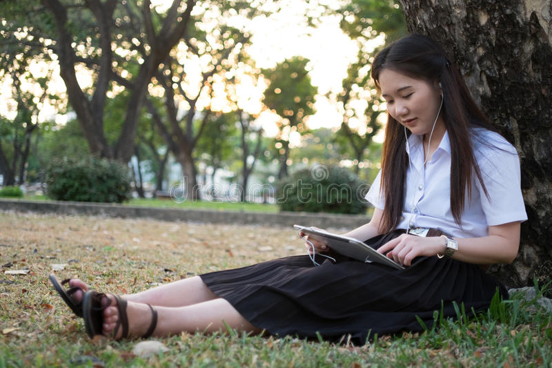 Asiatisk kvinna som använder minnestavlan och lyssnar till musik arkivfoto