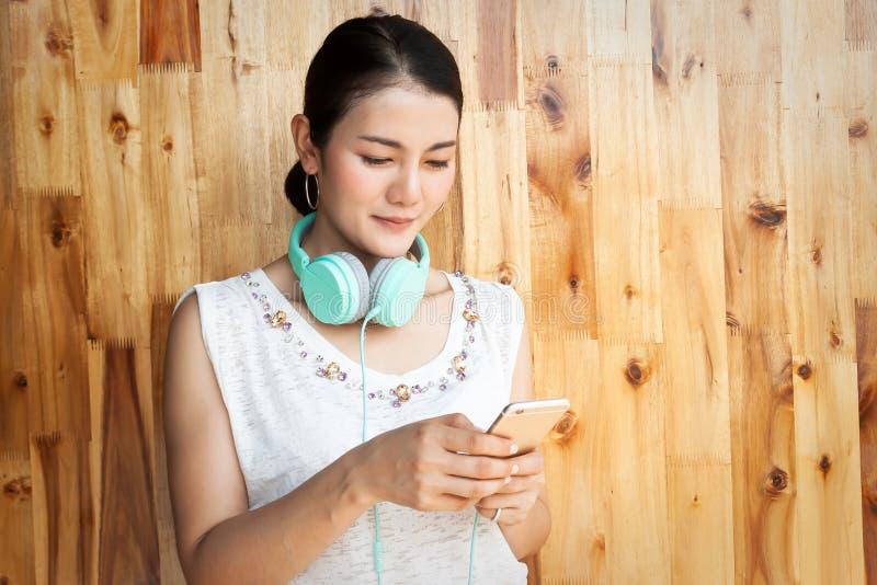 Asiatisk kvinna som använder mobiltelefonen med hörlurar på hennes hals Teknologi och livsstil arkivbilder