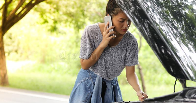 Asiatisk kvinna som använder mobiltelefonen, medan se och stressad mansi royaltyfri bild