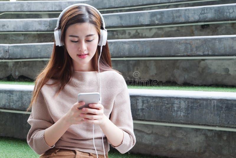Asiatisk kvinna som använder mobiltelefonen och headphonen som lyssnar royaltyfria bilder
