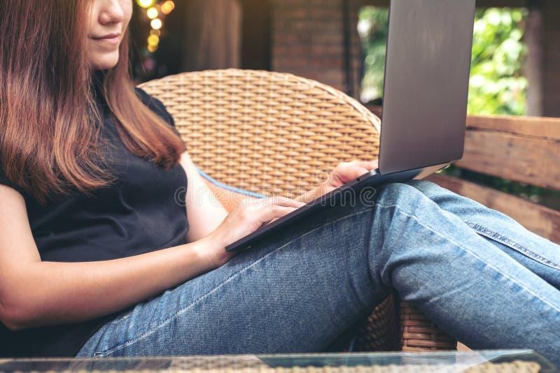 Asiatisk kvinna som använder och skriver på bärbar datortangentbordet, medan sitta som är utomhus- med mening avkopplat arkivbilder