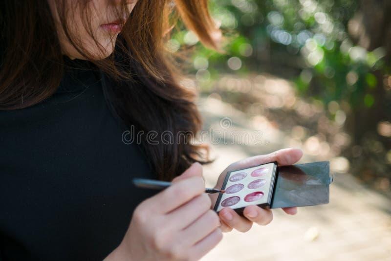 Asiatisk kvinna som använder skönhetsmedlet arkivbild