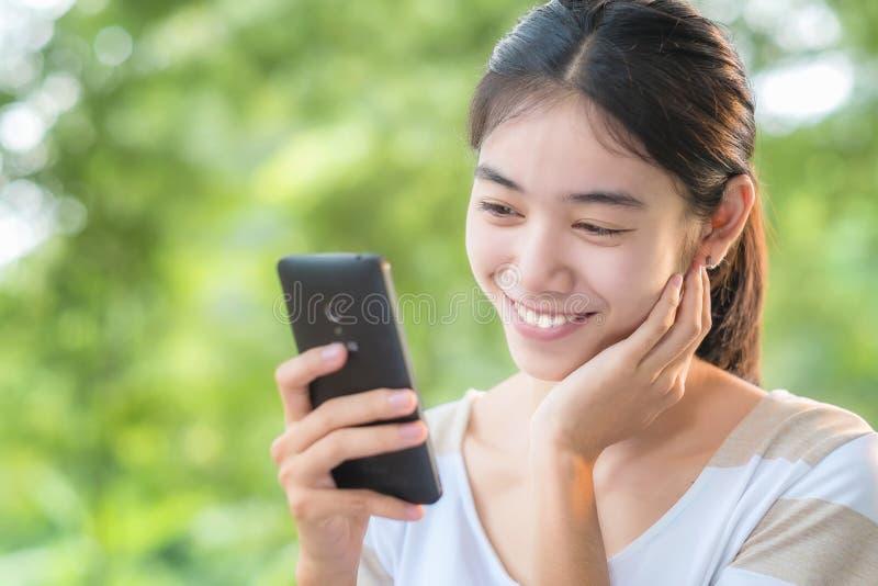 Asiatisk kvinna som använder smartphone royaltyfria foton