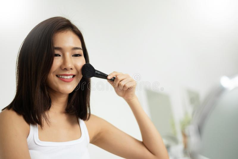 Asiatisk kvinna som applicerar makeup med en borste royaltyfri foto