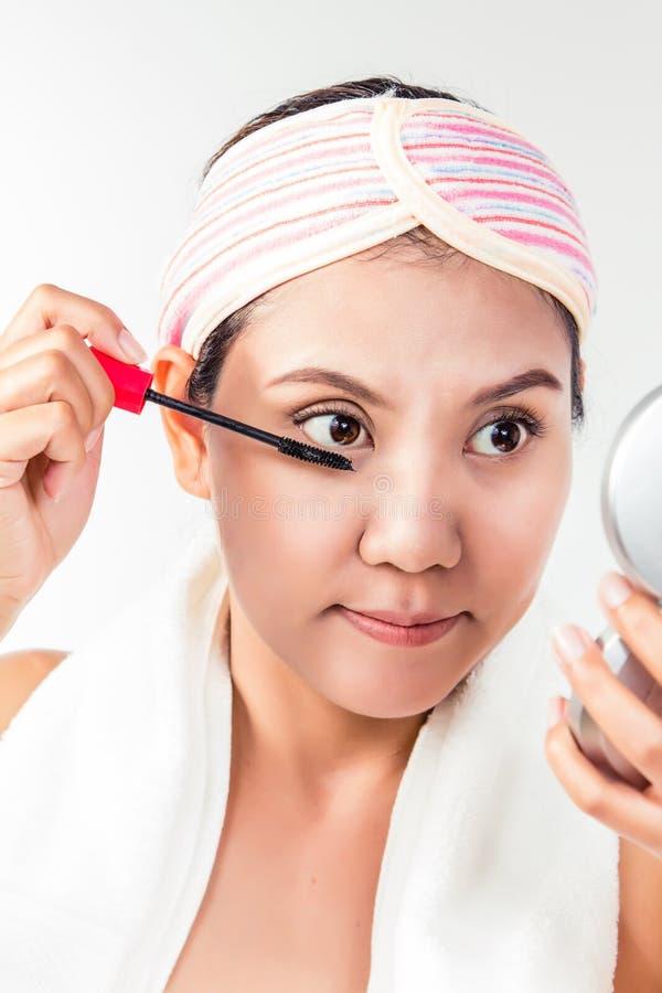 Asiatisk kvinna som applicerar mascaramakeup på ögon vid borsten royaltyfri foto