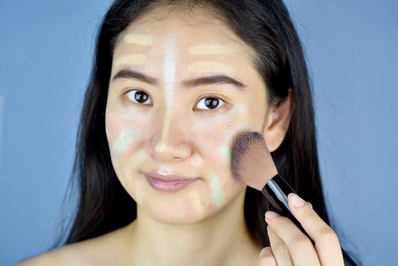 Asiatisk kvinna som applicerar skönhetsmedelmakeup och använder färgkorrigeringstäckstiftet, framsidahud som förbereder sig för m arkivbild