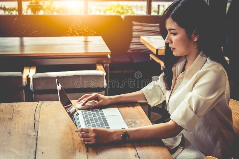 Asiatisk kvinna som arbetar med b?rbara datorn i coffee shop Folk och livsstilbegrepp Utomhus funktionsdugligt och frilans- tema royaltyfri bild