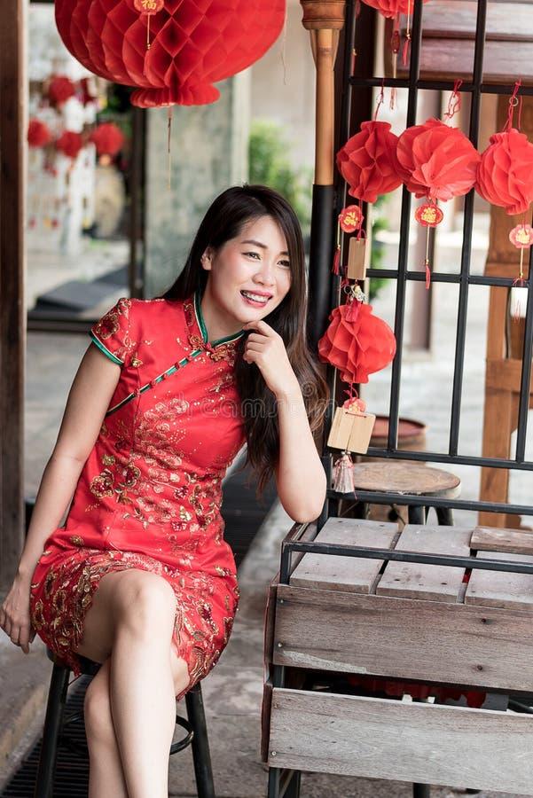 Asiatisk kvinna som bär röd traditionell festival för nytt år för klänning n kinesisk royaltyfri fotografi
