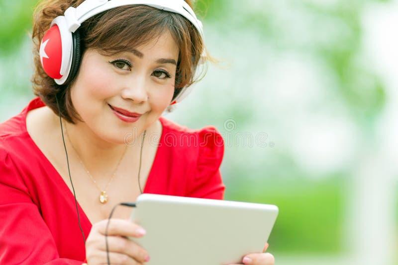 Asiatisk kvinna som bläddrar minnestavlan royaltyfri bild