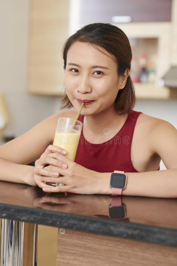Asiatisk kvinna som dricker den smakliga fruktcoctailen fotografering för bildbyråer