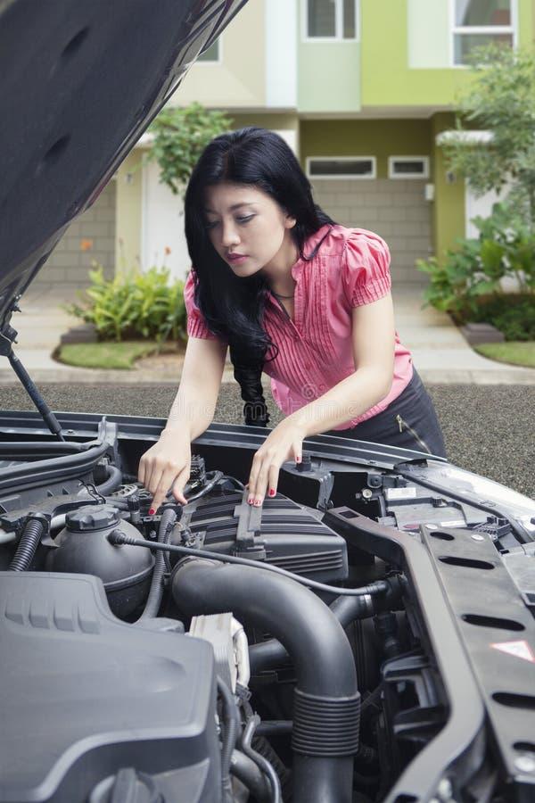 Asiatisk kvinna som försöker att fixa den brutna ner bilen framme av hennes hus royaltyfri bild