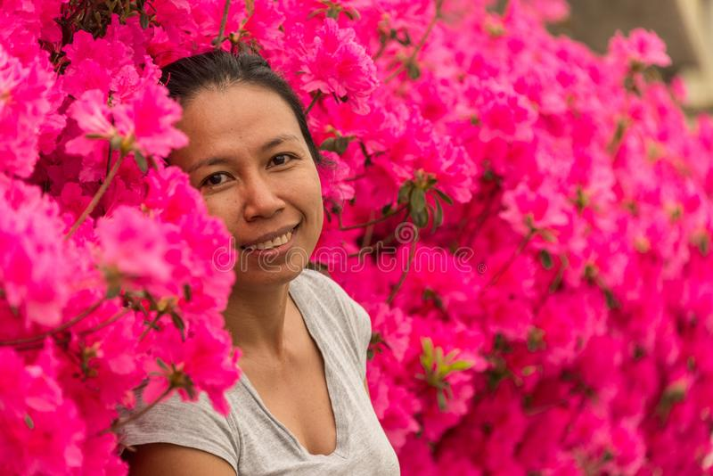 Asiatisk kvinna som framme står av rosa azaleablommor i tshirt på dag för varm vår arkivfoton