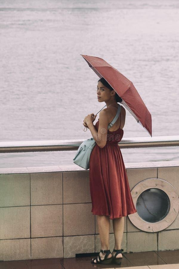 Asiatisk kvinna som går vid floden med paraplyet under regn under regnig säsong på semester för sommardag Elegant kinesisk dam i  royaltyfria bilder